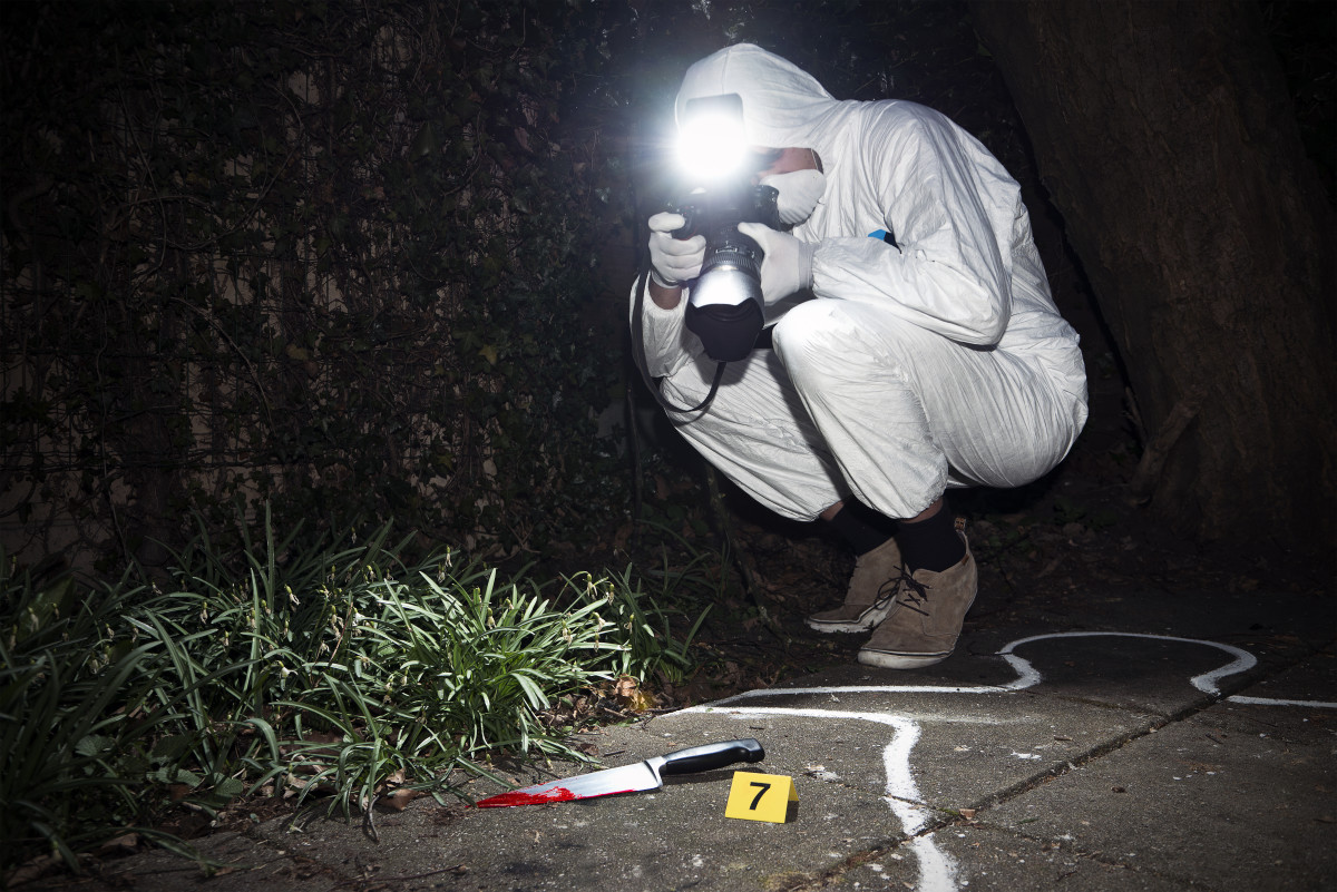 Forensics researcher photographing a blood-stained knife at a murder scene. (Photo: Corepics VOF/Shutterstock)
