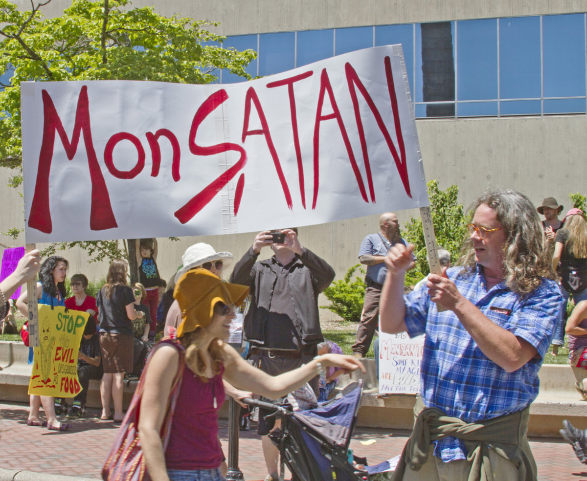 "Genetically modified food protesters hold up a sign  calling Monsanto ""MonSATAN""at a GMO protest rally on May 25, 2013, in  downtown Asheville, North Carolina. (Photo: J. Bicking/Shutterstock)"