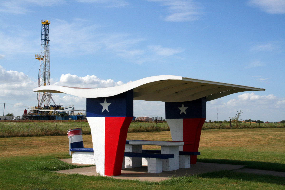 A picnic table at a rest stop in Texas with an oil rig in the background. (Photo: Brandon Seidel/Shutterstock)
