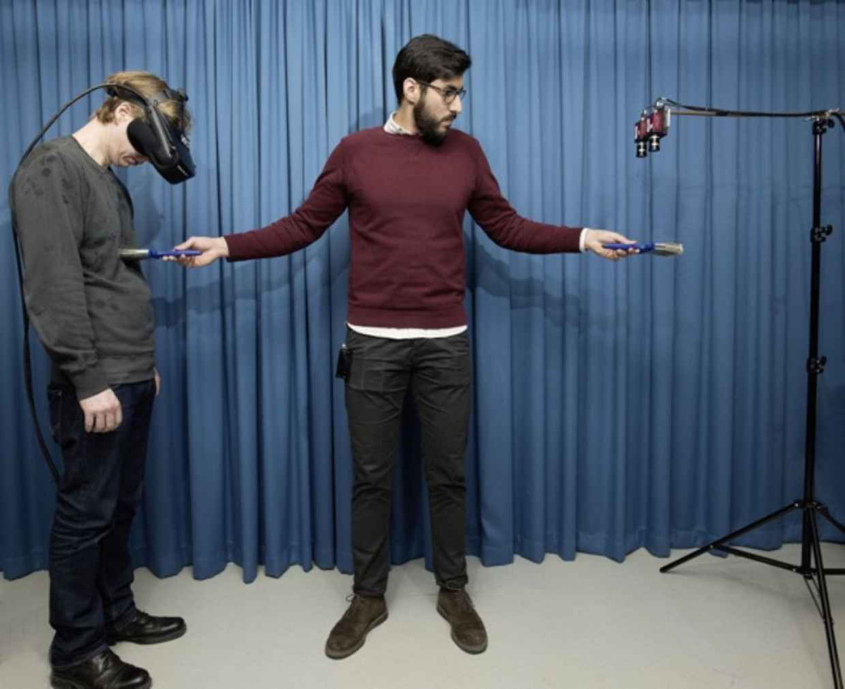 Study co-author Zakaryah Abdulkarim (middle) creates the invisible body illusion on a participant (left) wearing a set of head-mounted displays connected to a pair of cameras. (Photo: Staffan Larsson)