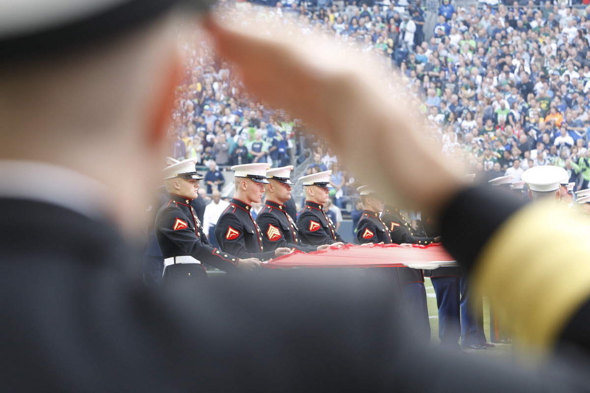 U.S. Marines salute and hold the American Flag at a Monday night football game in Seattle, Washington. (Photo: Kevin Casey/Getty Images)