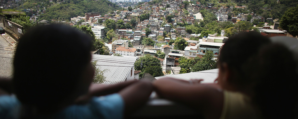 Members of the Das Neves family look out of their home in the Prazeres favela on October 19, 2013, in Rio de Janeiro, Brazil. The family participates in Brazil's Bolsa Familia program and said that the program assisted them in purchasing a new home after their previous one was condemned. (Photo: Mario Tama/Getty Images)