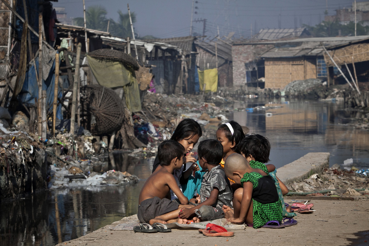 Children play outside their home, next  to a polluted canal which empties out into the Buriganga river in the Hazaribagh neighborhood of Dhaka, Bangladesh. (Photo: Getty Images)