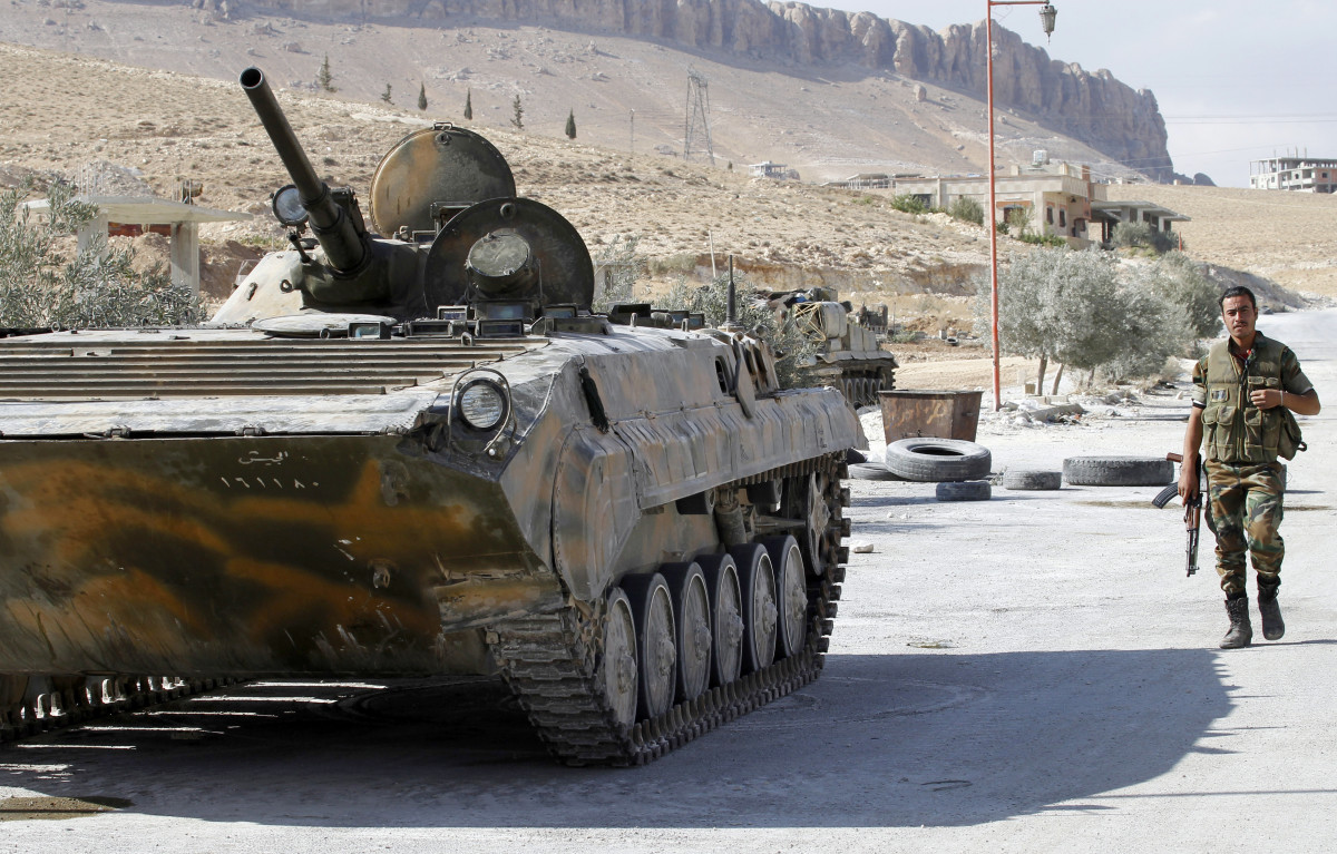 A Syrian soldier walks toward a Russian-made Syrian Army armored personnel carrier stationed along a street leading into Syria's ancient Christian town of Maalula. (Photo: Anwar Amro/AFP/Getty Images)