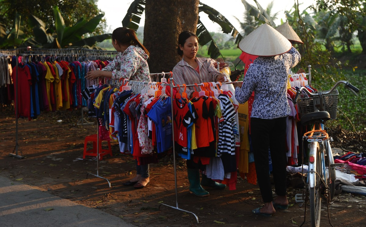 This picture taken on March 30, 2015, shows women selling clothes at their roadside stands in Quoc Oai district, on the outskirts of Hanoi. (Photo: Hoang Dinh Nam/AFP/Getty Images)
