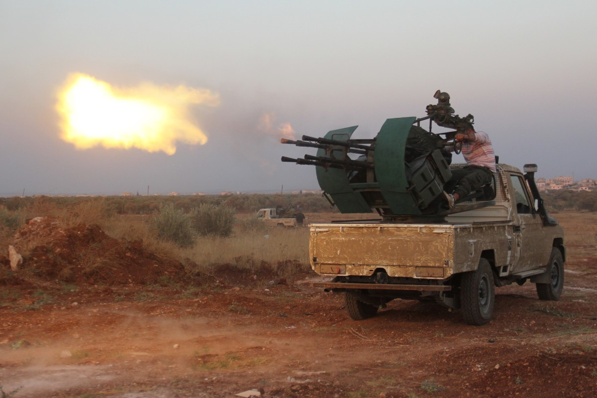 Rebel fighters fire a machine gun during clashes with Syrian pro-government forces on the frontline facing Deir al-Zoghb, a government-held area in the northwestern Idlib province, on August 31, 2015. (Photo: Omar Haj Kadour/AFP/Getty Images)