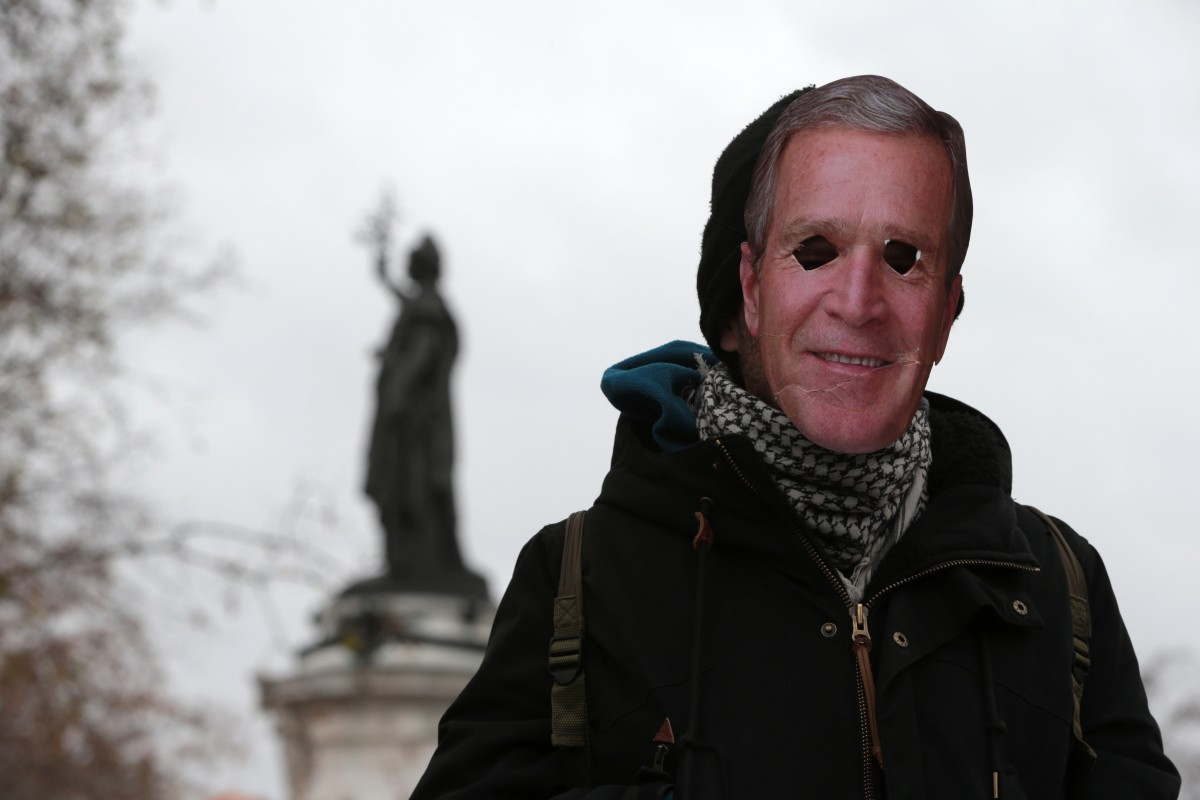 A protestor wearing a mask of former President George W. Bush, Paris, November 29, 2015. (Photo: Joel Saget/AFP/Getty Images)