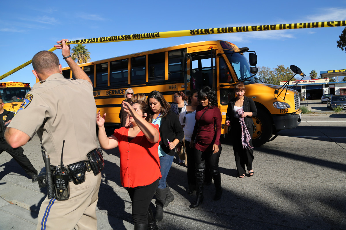 Employees and other people are evacuated by bus from the site of a mass shooting at the Inland Regional Center on December 2, 2015, in San Bernardino, California. (Photo: David McNew/Getty Images)