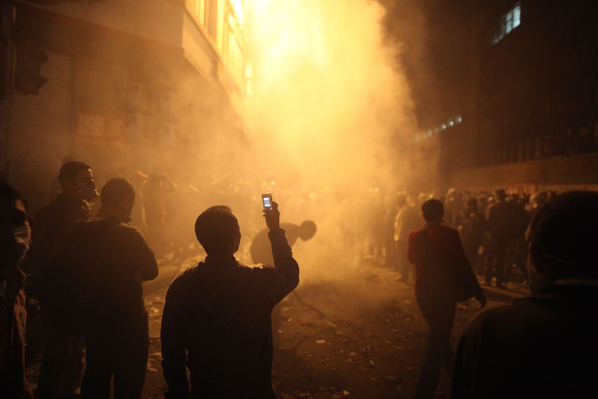 A youth films the aftermath of a tear gas volley fired by police on protestors in Muhammed Mahmoud Street near Tahrir Square on November 23, 2011, in Cairo, Egypt. (Photo: Peter Macdiarmid/Getty Images)