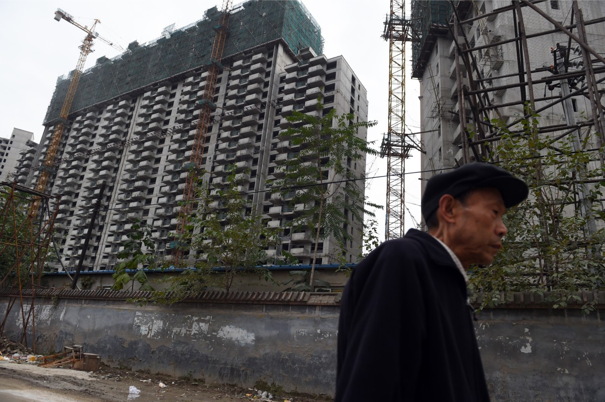 A man walks past a construction site for apartment buildings in Beijing on October 25, 2015. (Photo: Greg Baker/AFP/Getty Images)