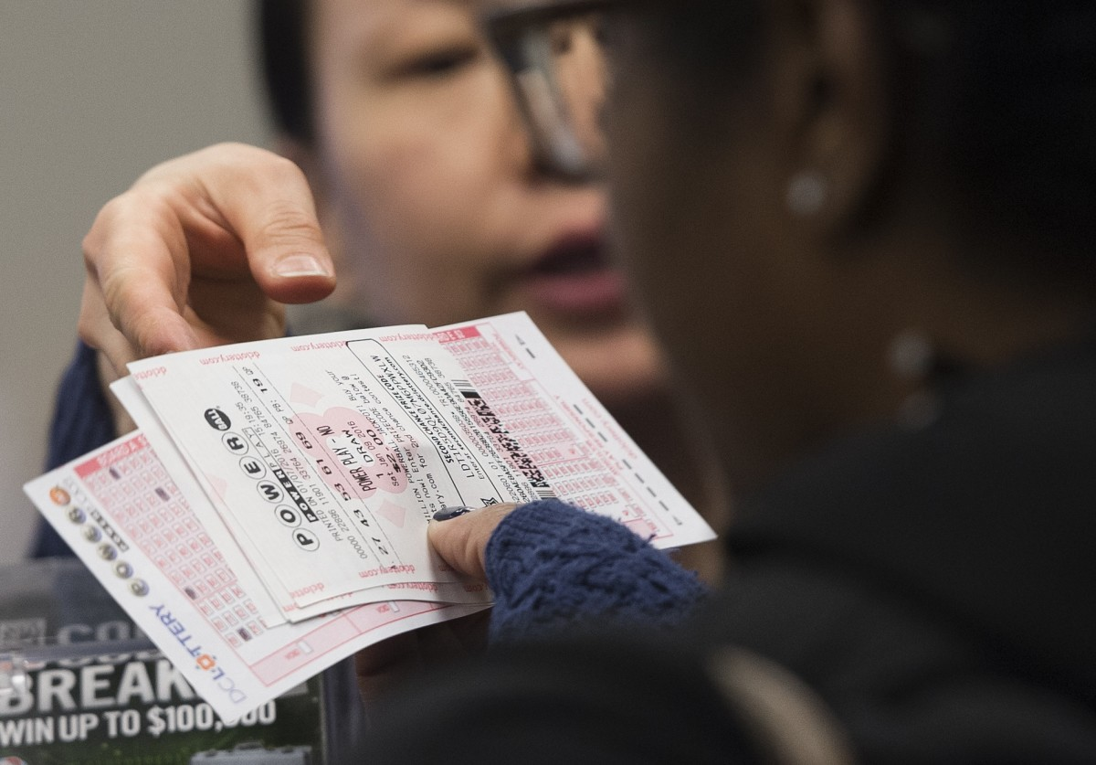 A woman purchases a Powerball lottery ticket at a convenience store in Washington, D.C. (Photo: Saul Loeb/AFP/Getty Images)