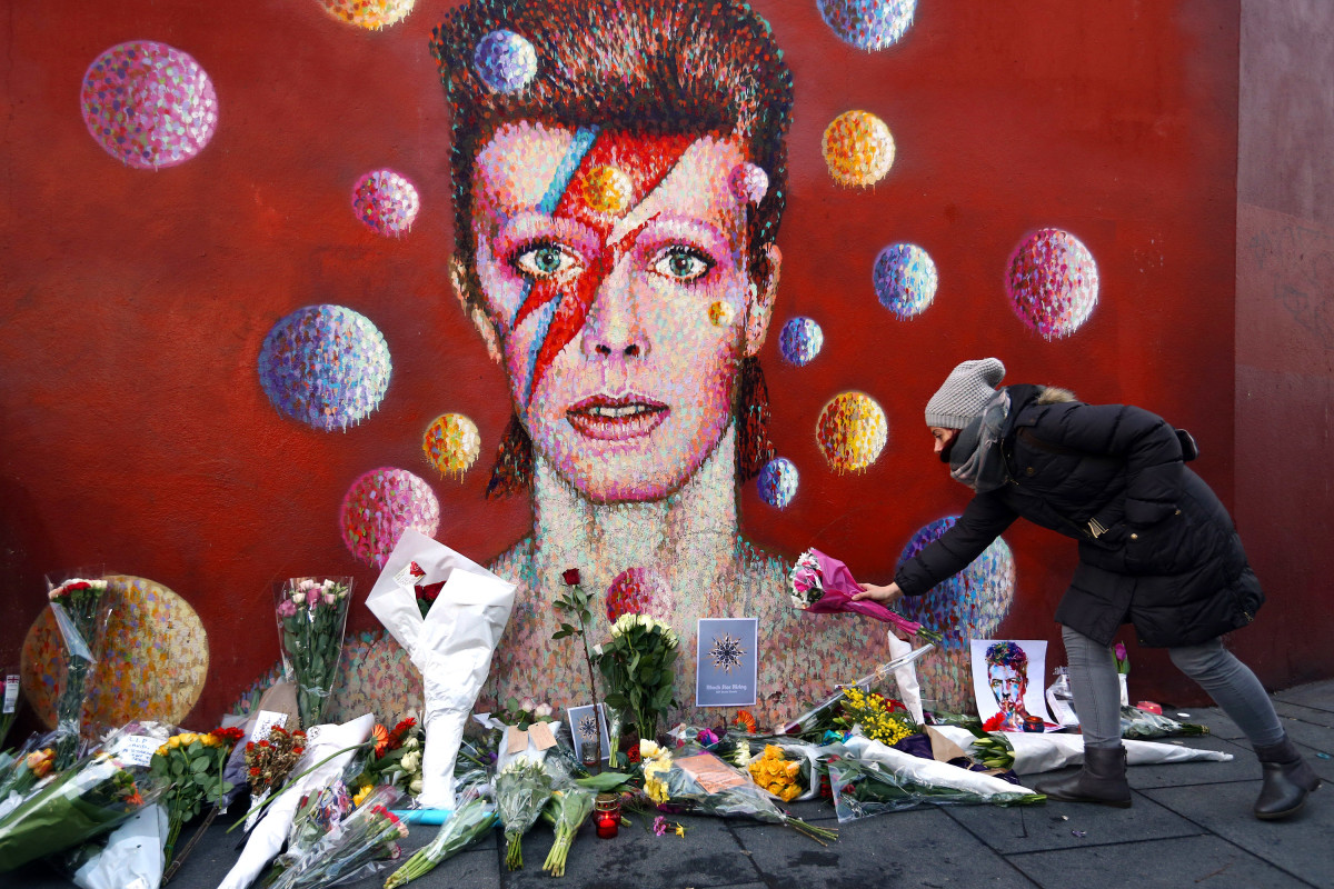 A woman leaves flowers beneath a mural of David Bowie in Brixton on January 11, 2016, in London, England. (Photo: Carl Court/Getty Images)