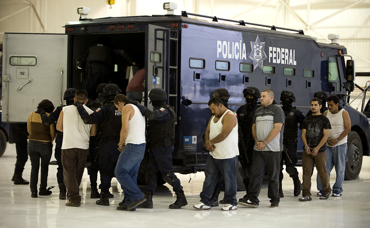 Nine alleged drug traffickers, members of the Sinaloa Cartel, are escorted to a police truck after being presented to the press in Mexico City, on July 12, 2010. (Photo: Luis Acosta/AFP/Getty Images)