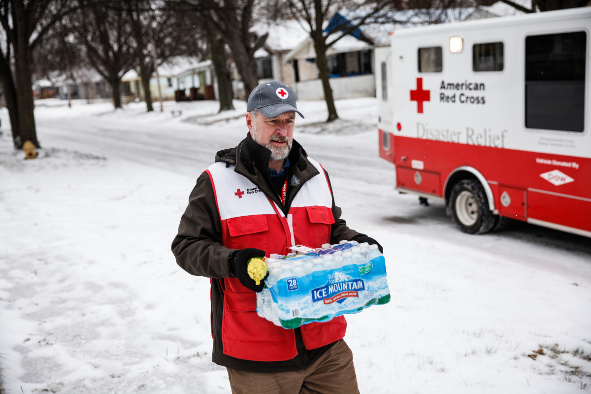 American Red Cross volunteer John Lohrstorfer walks down Maryland St. on Flint's north side bringing bottled water and filters to homes on January 21, 2016. (Photo: Sarah Rice/Getty Images)