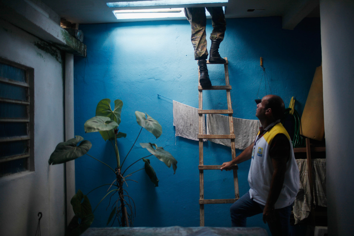 A city health worker secures a ladder as a Brazilian Air Force soldier climbs to inspect a rooftop in search for potential breeding grounds of Zika-carrying mosquitos on February 2, 2016, in Recife, Brazil. (Photo: Mario Tama/Getty Images)