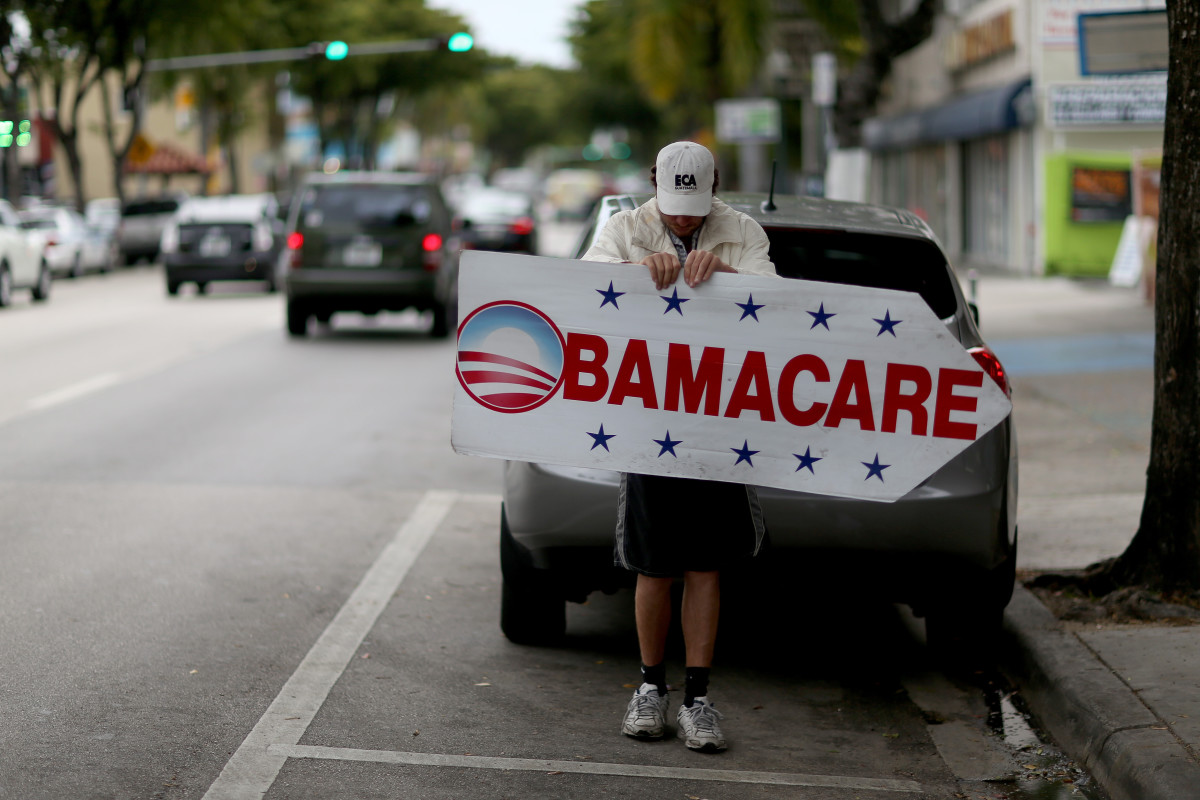 A man holds a sign directing people to an insurance company where they can sign up for the Affordable Care Act on February 5, 2015, in Miami, Florida. (Photo: Joe Raedle/Getty Images)