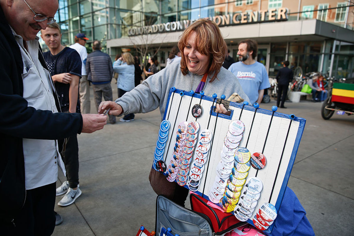 Daphne Lundy of Kansas City, Missouri, sells  buttons outside the Colorado Convention Center on February 13, 2016. (Photo: Marc  Piscotty/Getty Images)