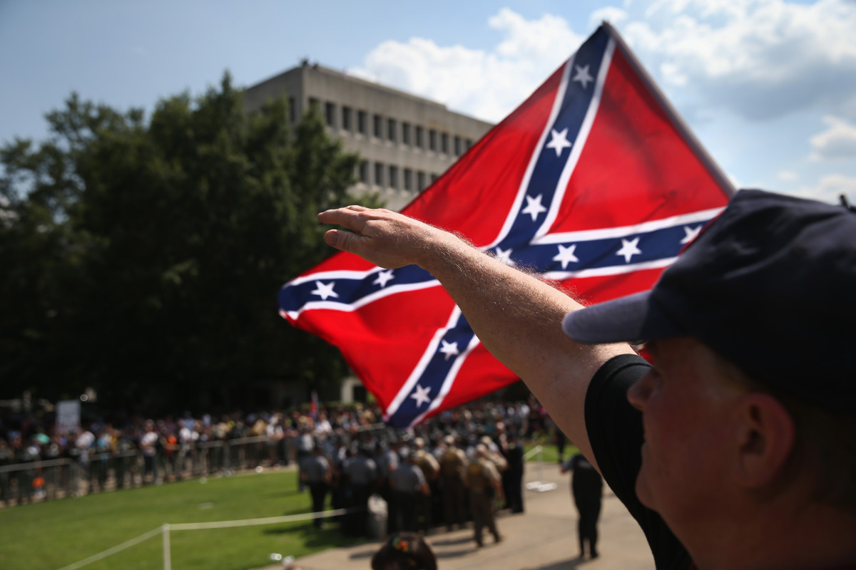 A member of the Ku Klux Klan gives a Nazi  salute as the Klan members fly the Confederate flag during a  demonstration at the state capitol building on July 18, 2015, in  Columbia, South Carolina. (Photo: John Moore/Getty Images)