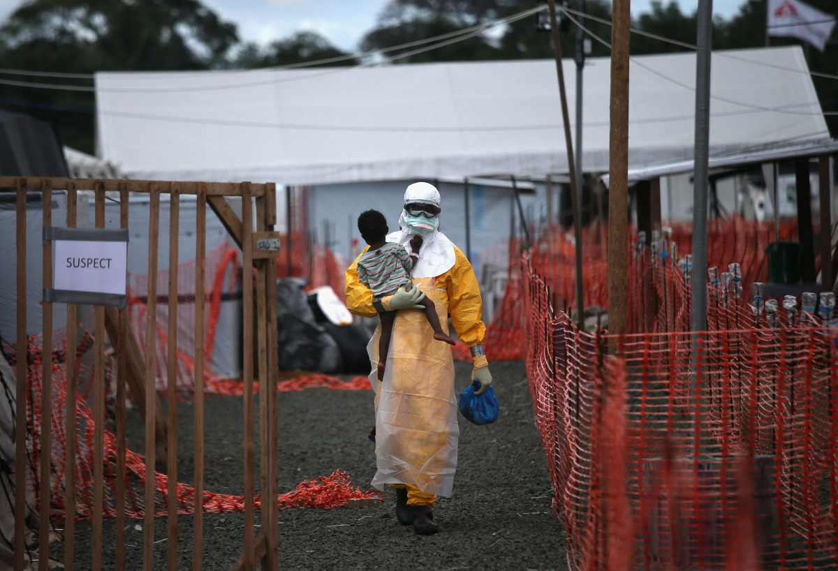 A Doctors Without Borders health worker in protective clothing carries a child suspected of having Ebola in the treatment center on October 5, 2014, in Paynesville, Liberia. (Photo: John Moore/Getty Images)
