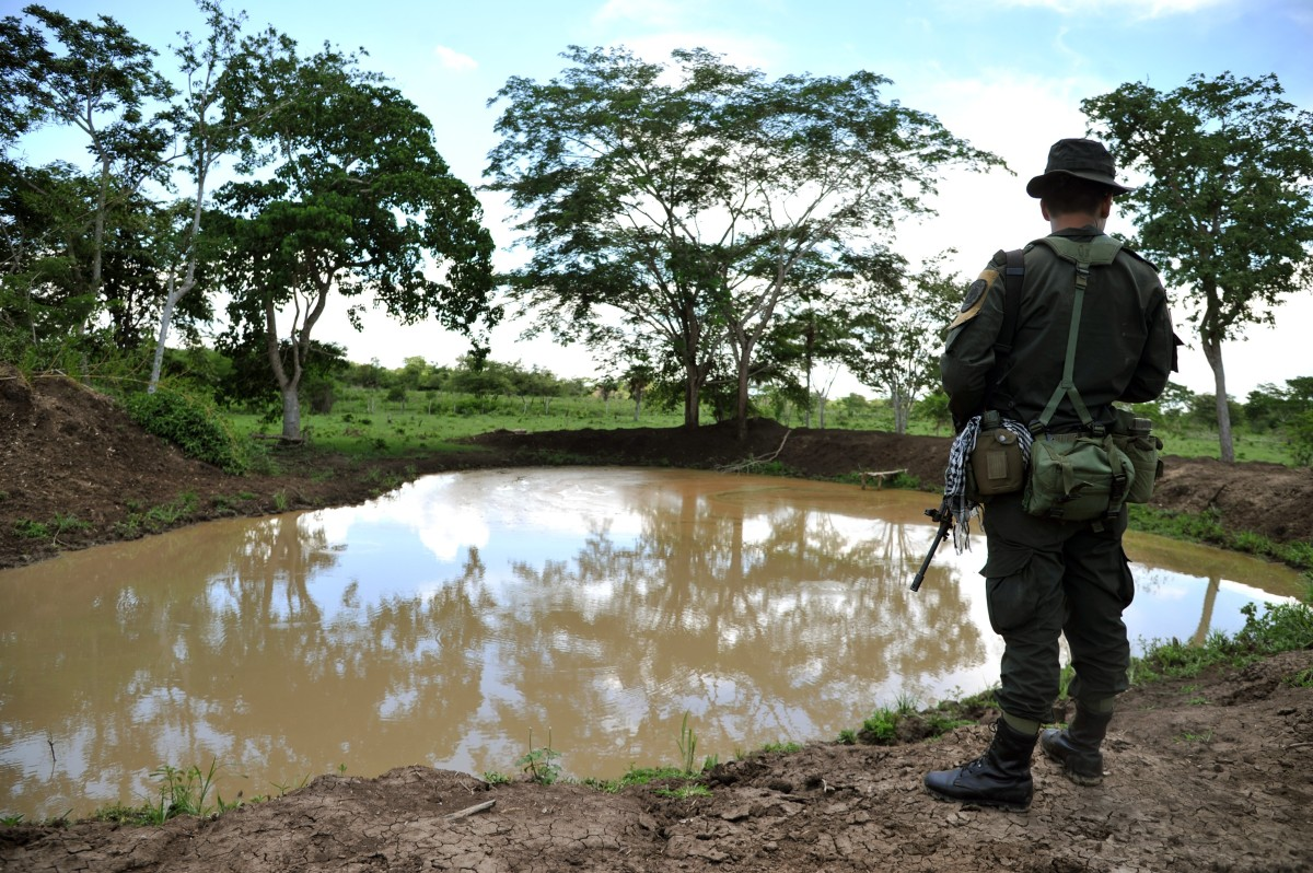 A police officer stands guard during a government land restitution  process. Farmers were displaced under pressure and threats from former  paramilitary commander Rodrigo Tovar Pupo. (Photo: Guillermo Legaria/AFP/Getty Images)
