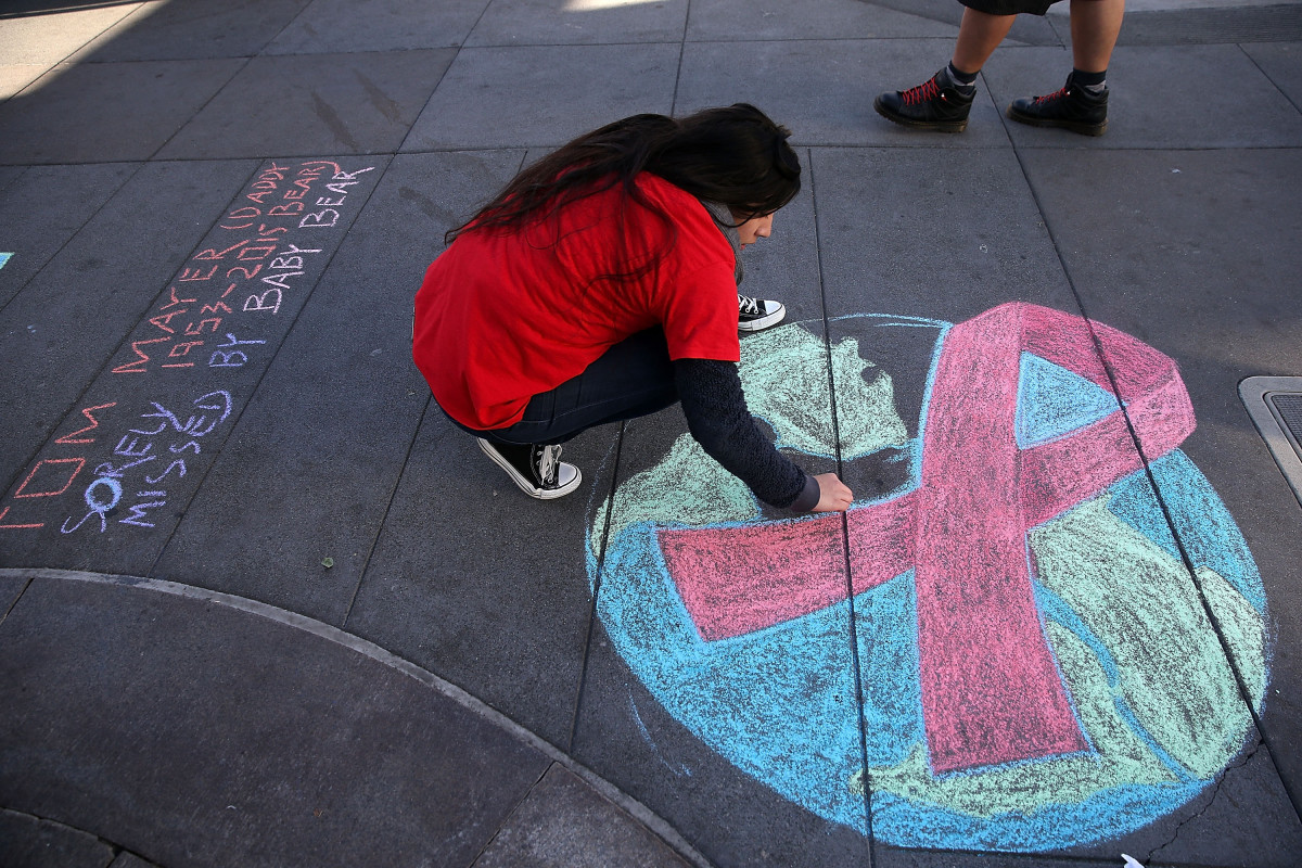 Angelica Tome does a chalk drawing of a red AIDS ribbon on Castro Street on World AIDS day in San Francisco, California. (Photo: Justin Sullivan/Getty Images)