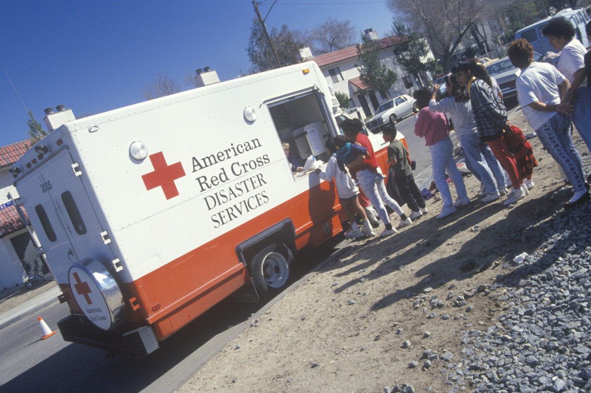 A worker in an American Red Cross disaster service vehicle handing out supplies to people after a 1994 earthquake. (Photo: Joseph Sohm/Shutterstock)