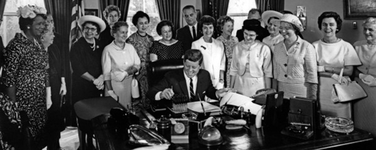 President John F. Kennedy signing the 1963 Equal Pay Act, a law top  women leaders saw as part of a larger movement against underpay and  overwork. (Photo: Public Domain)