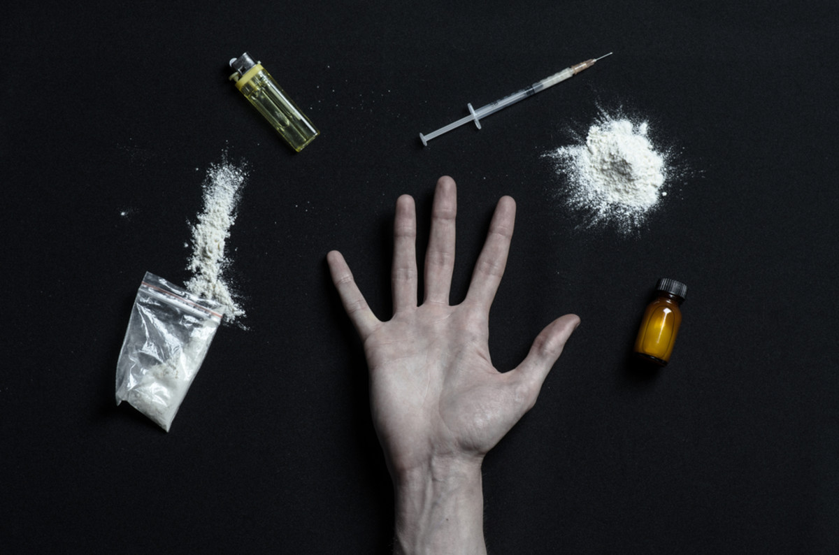 a hand surrounded by drugs symbolizing addiction.