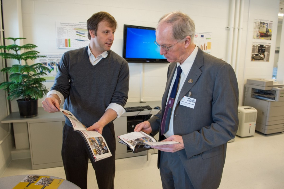 Photo showing Representative Bill Foster and another man looking at booklets in an office