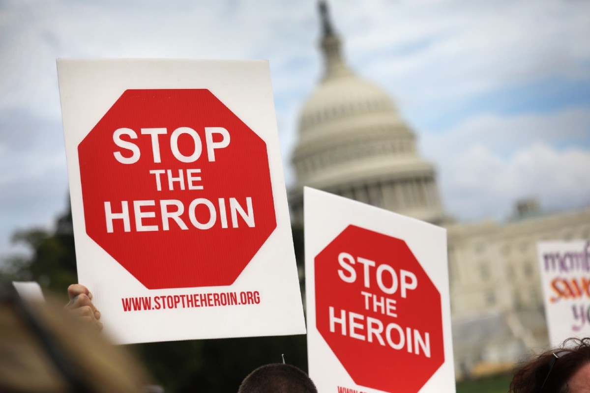 "Photo showing protest signs saying, ""STOP THE HEROIN,"" with the Capitol building in the background"