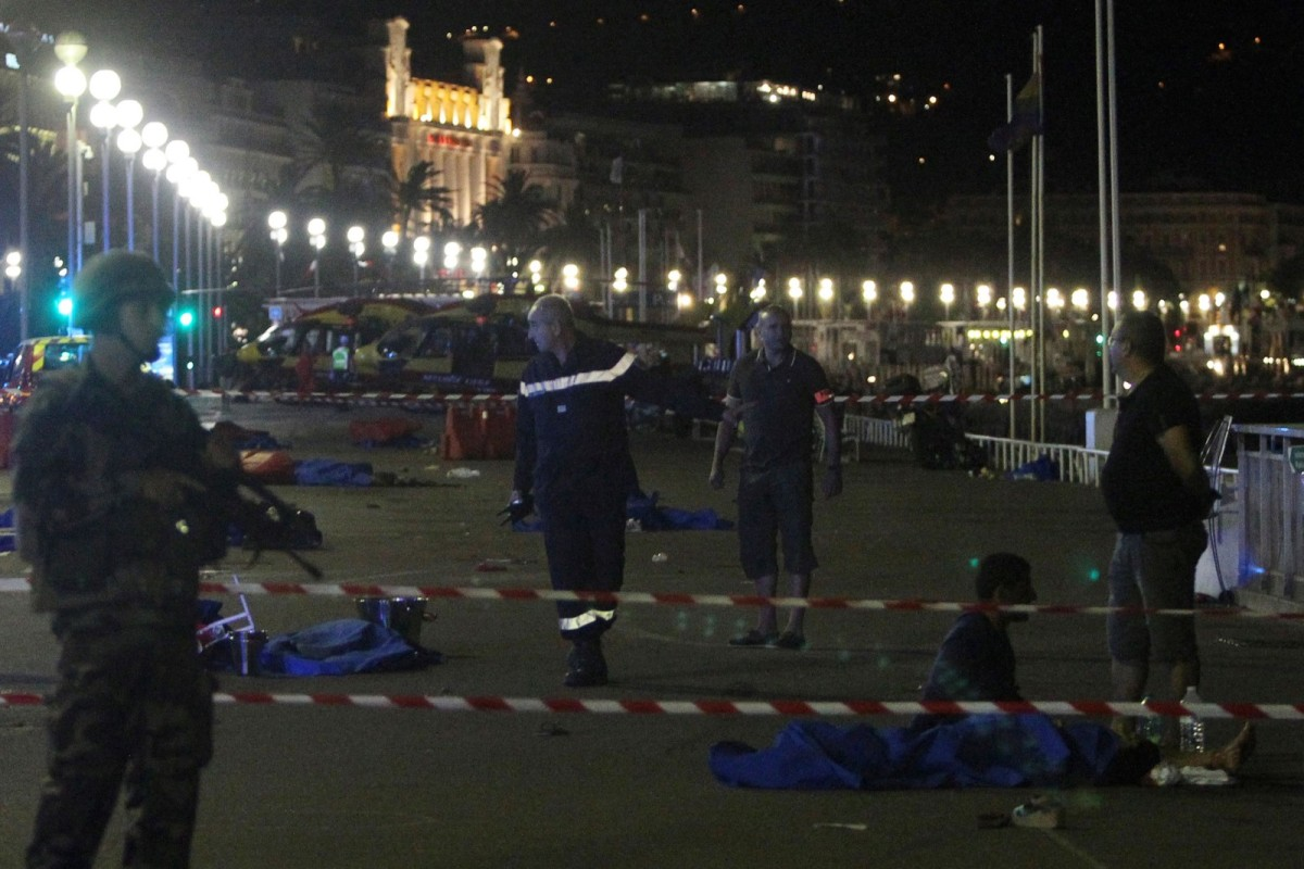 Soldiers, police officers, and firefighters walk near dead bodies covered with a blue sheets on the Promenade des Anglais seafront in the French Riviera town of Nice on July 15, 2016, after a van drove into a crowd watching a fireworks display.
