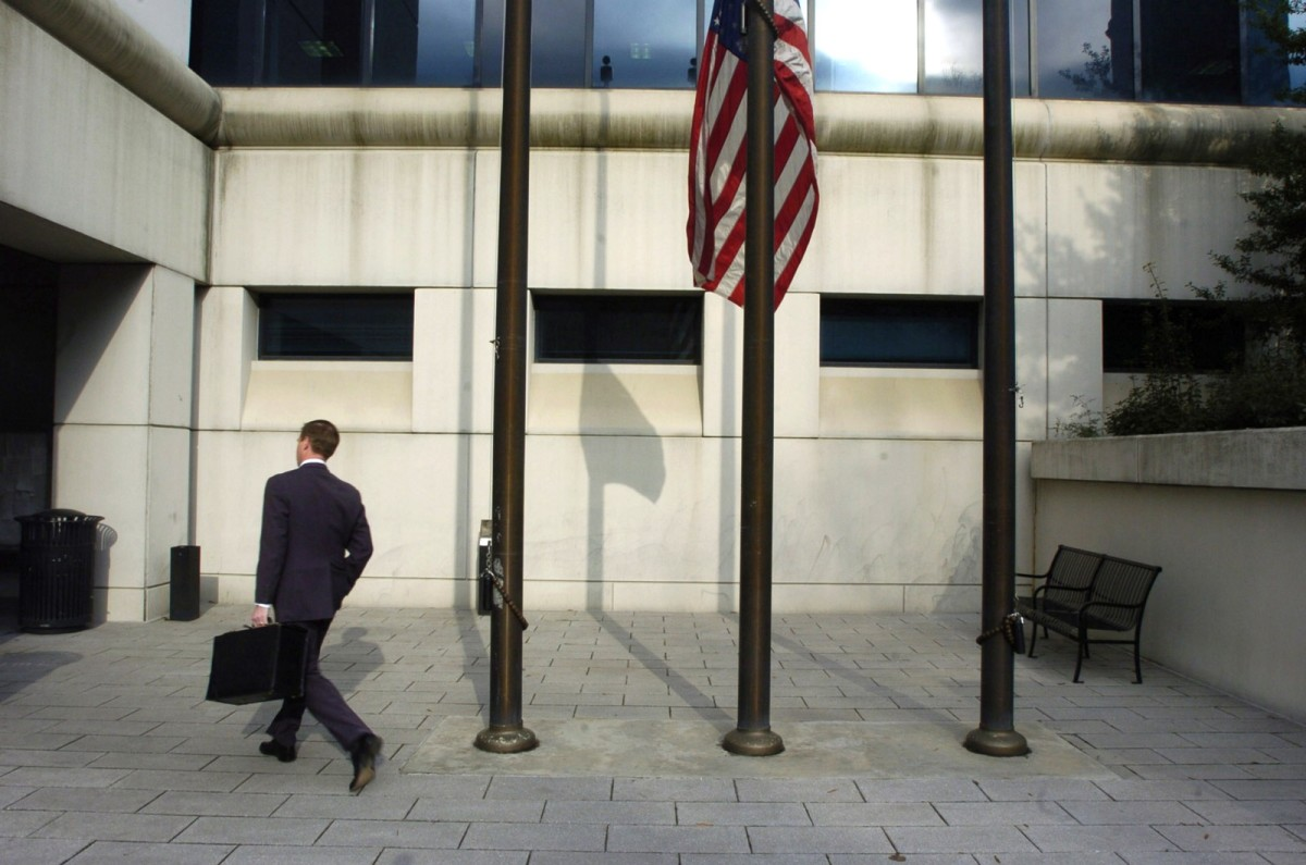 A businessman walks past a U.S. flag flying at half mast as people return to work at the Fulton County Superior Courthouse on March 14th, 2005, in Atlanta, Georgia.