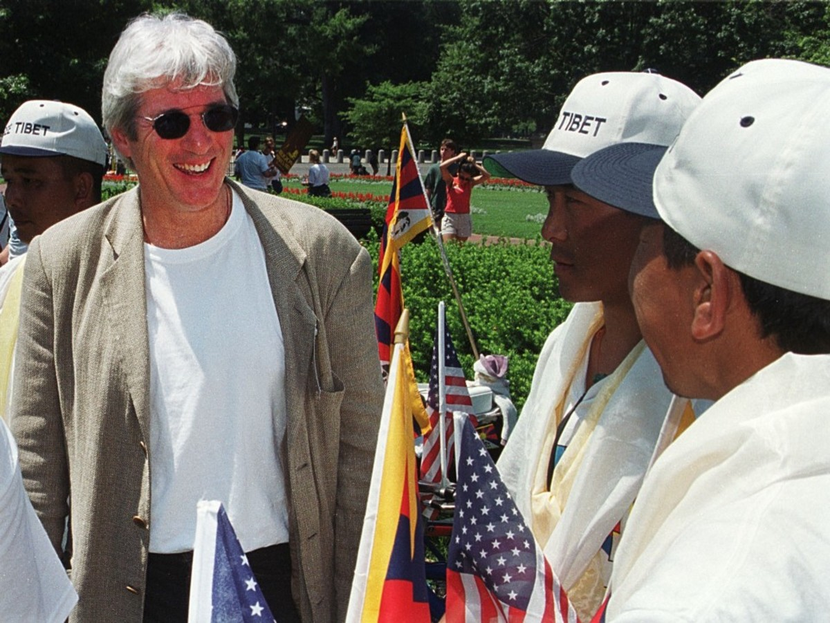 Richard Gere laughs with Tibetan protesters before giving a speech at a rally to free Tibet on July 1st, 2000.