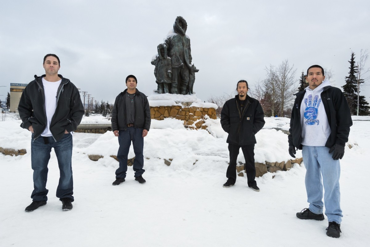 From left: Kevin Pease, Eugene Vent, George Frese, and Marvin Roberts stand in front of Malcolm Alexander's Unknown First Family sculpture.