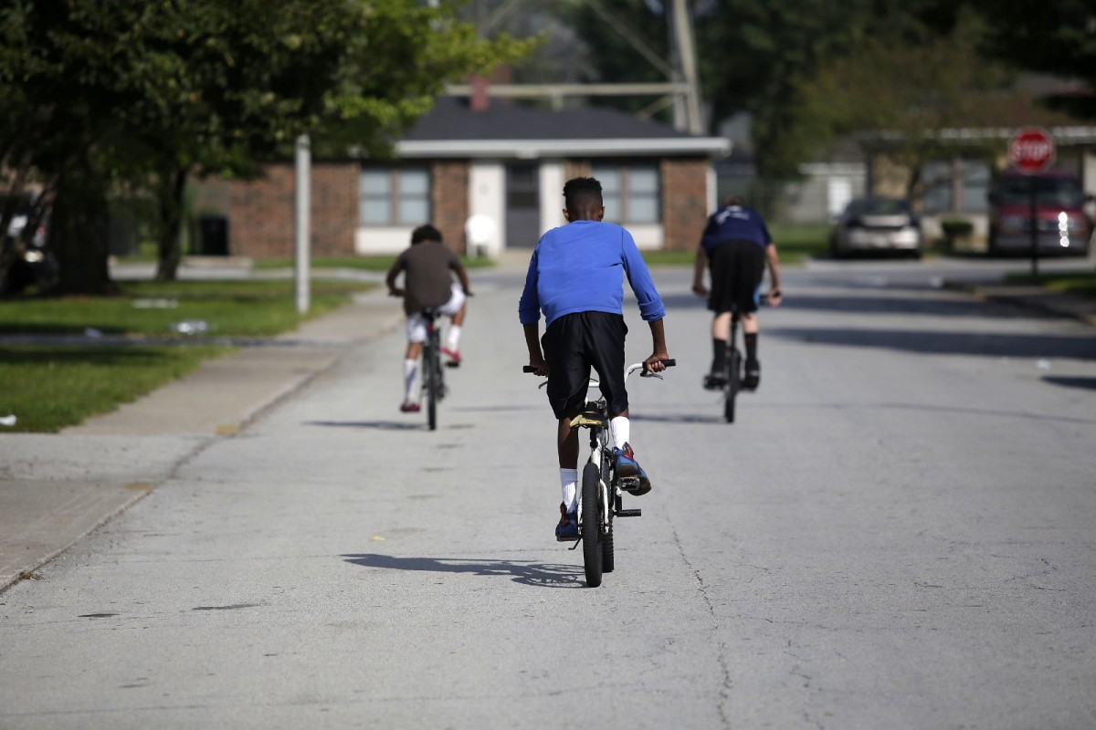 A group of boys ride their bikes through the West Calumet Housing Complex.