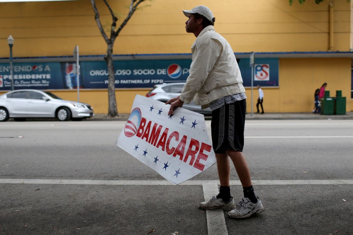 A man holds a sign directing people to an insurance company where they can sign up for the Affordable Care Act, on February 5th, 2015, in Miami, Florida.