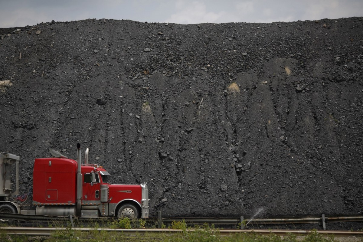 A truck drives by a mound of coal in Cattletsburg, Kentucky. (Photo: Luke Sharrett/Getty Images)