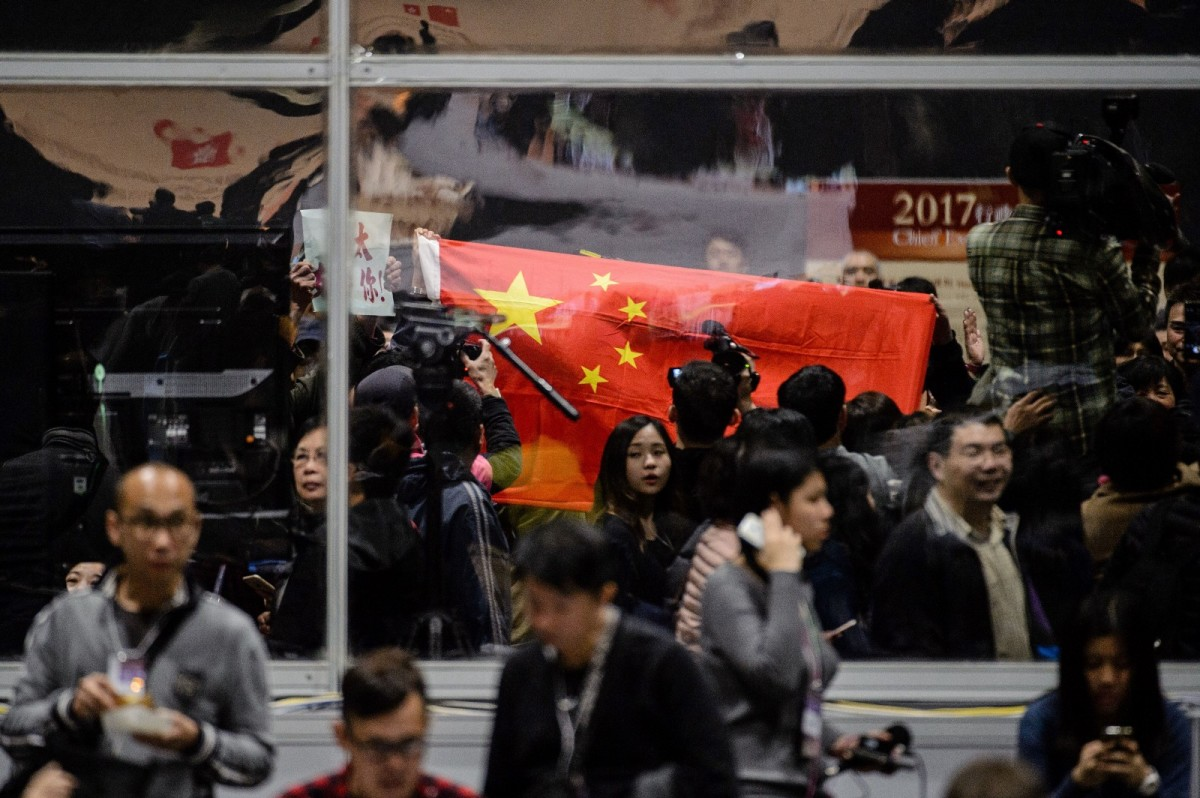 A Chinese flag is held up by Beijing supporters before the official announcement that Carrie Lam won the election in Hong Kong on March 26th, 2017. (Photo: Anthony Wallace/AFP/Getty Images)