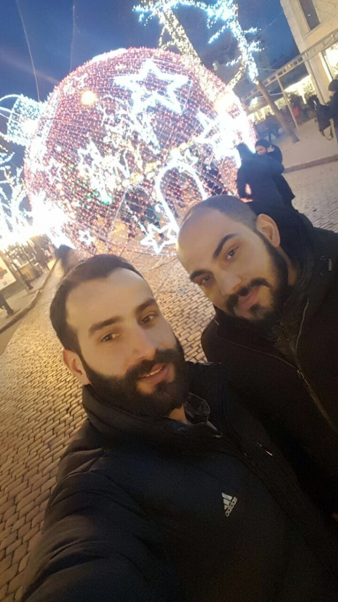 Photo showing two young men in front of a Christmas light display