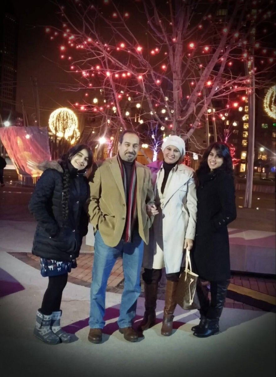 Photo showing a family of four in front of a tree lit for Christmas