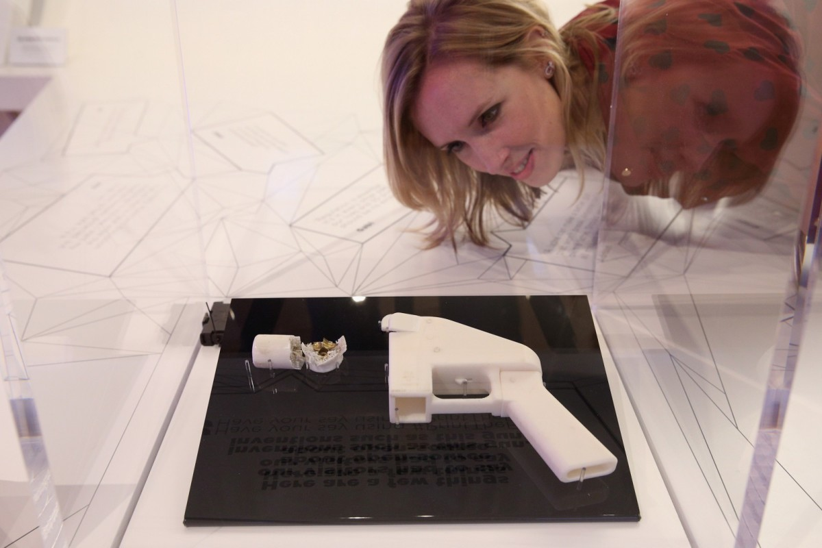 A woman admires a 3-D printed handgun on display in a museum.