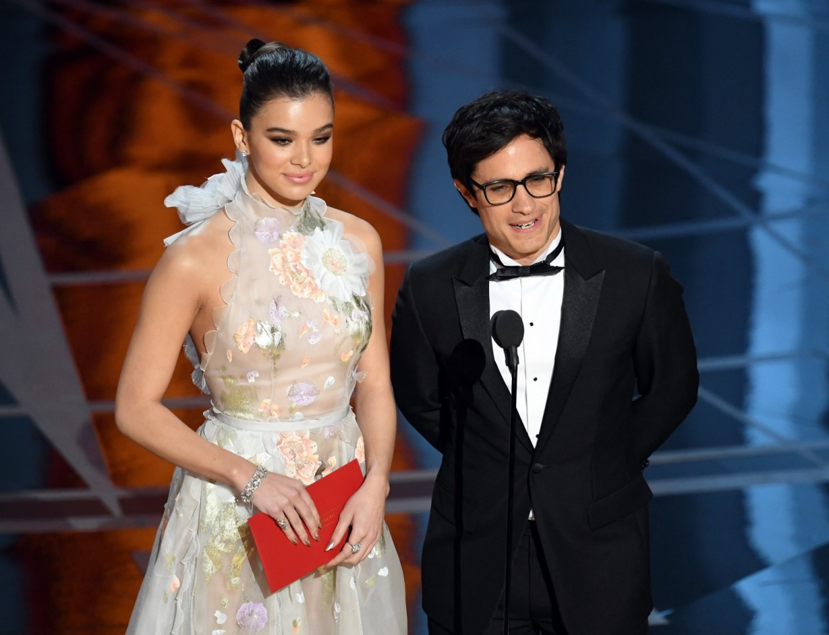 Hailee Steinfeld and Gael Garcia Bernal speak onstage during the Academy Awards.