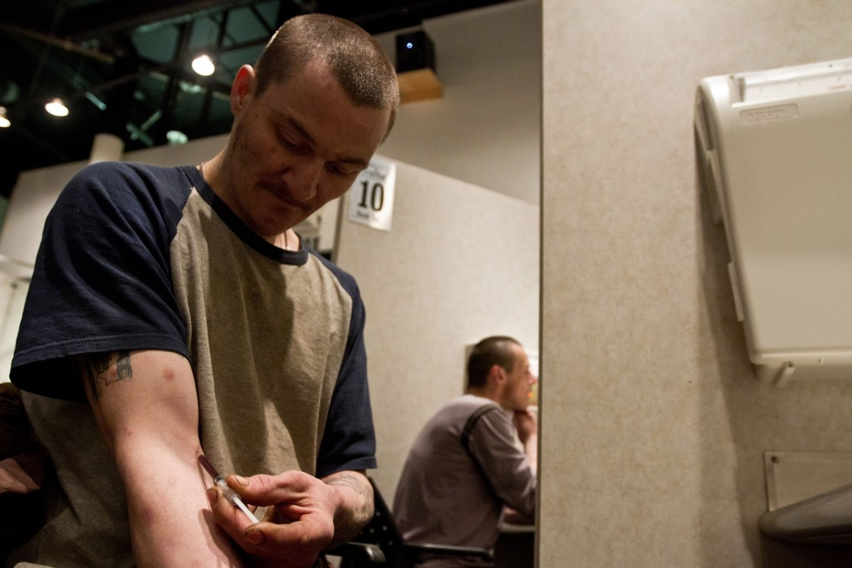 Photo showing a man injecting himself with a substance in a supervised injection booth in Vancouver, B.C.