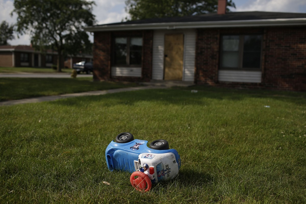 A toy police truck lays in the grass outside of a house at the West Calumet Housing Complex in East Chicago, Indiana.