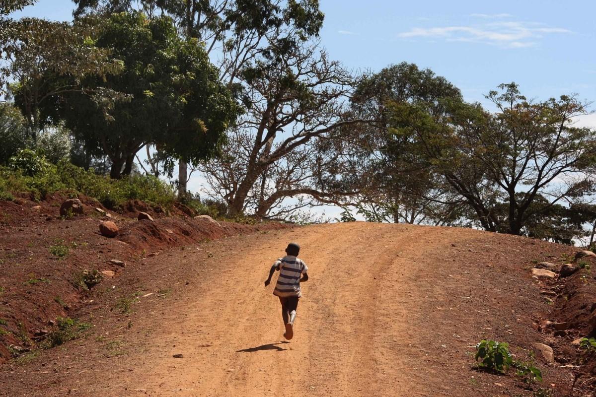 A boy runs along a dirt road in Kogelo, western Kenya.