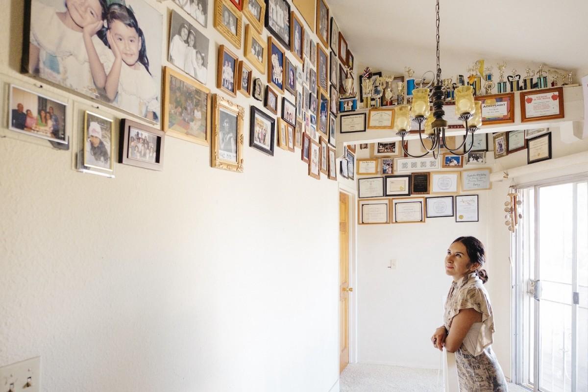 Bernabé mira las fotografías de su familia colocadas en lo alto de las paredes en la casa de Los Ángeles en la que ha vivido desde los diez años.