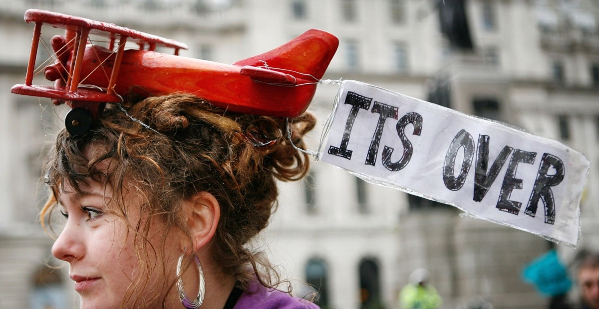 A climate change protestor wears a toy airplane on her head in London, December 8, 2007. (Photo: Peter Macdiarmid/Getty Images)