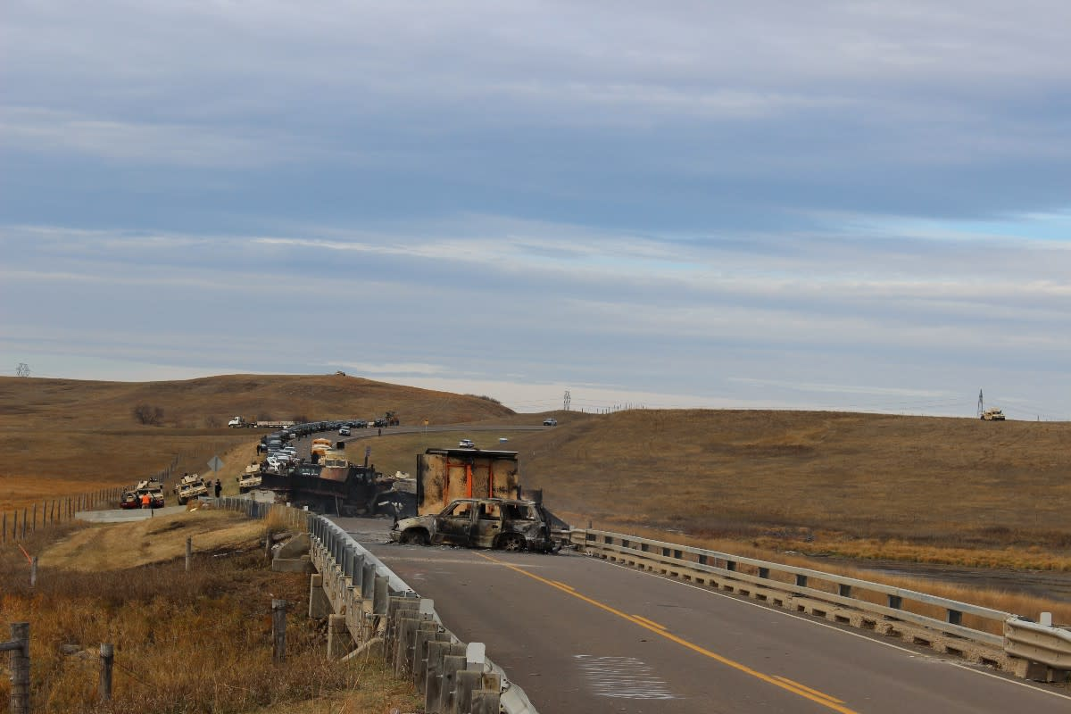 Cars sat ablaze the night of October 27th, 2016, on Highway 1806. Humvees, snipers, and police to the north, the Dakota Access Pipeline under construction beyond.