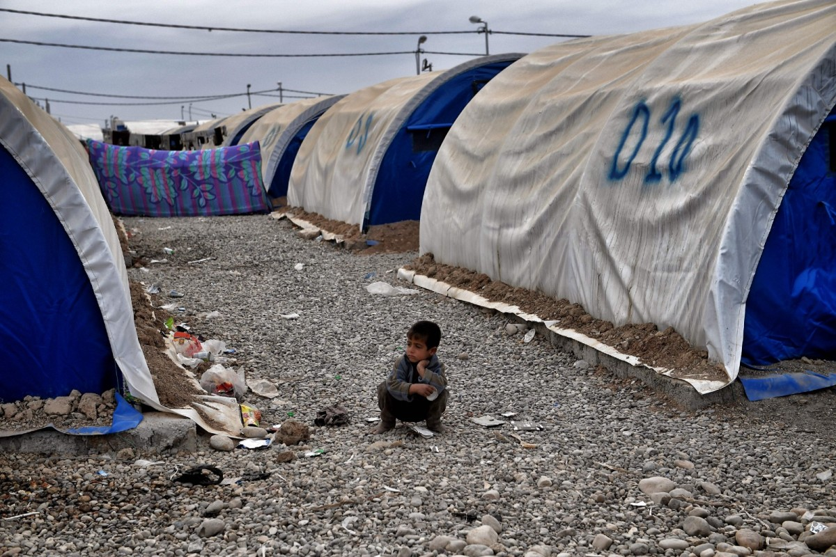 A young boy sits outside tents at the Hammam al-Alil camp for displaced people, south of Mosul, Iraq, on March 1st, 2017.