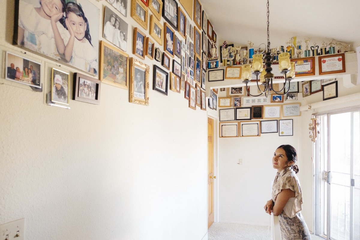 Bernabé looks at photographs of her family placed high on the walls in the Los Angeles home she's been in since the age of 10.